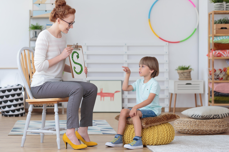 GP: Boy practicing correct pronunciation with speech therapist