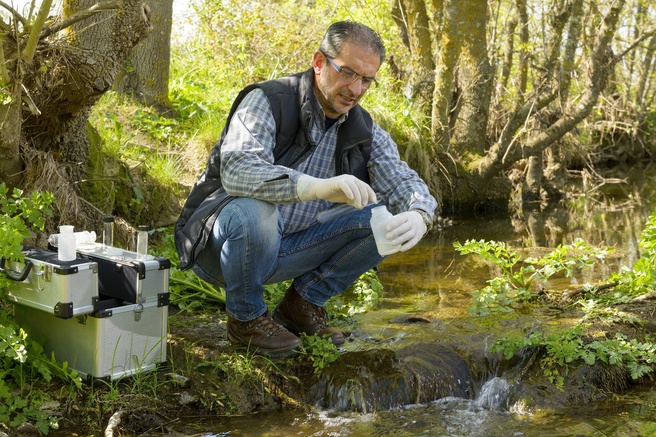 GP: Biologist take a sample in a river.