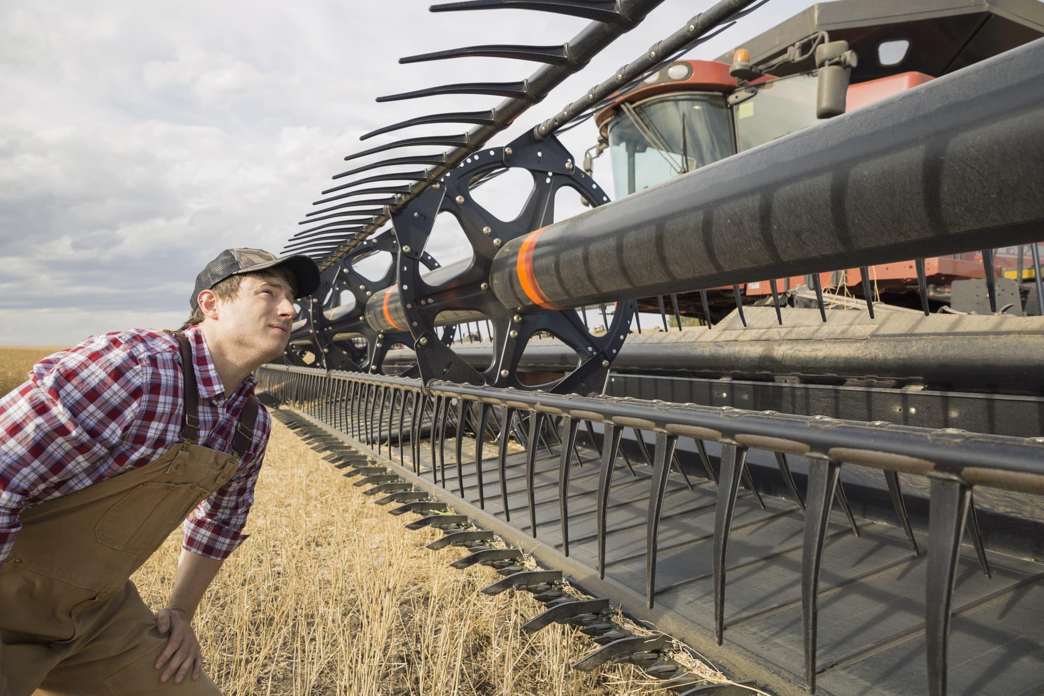 GP: Farmer examining equipment on combine harvester