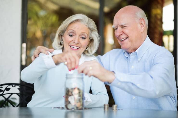 GP Senior Couple Saving Money In Jar