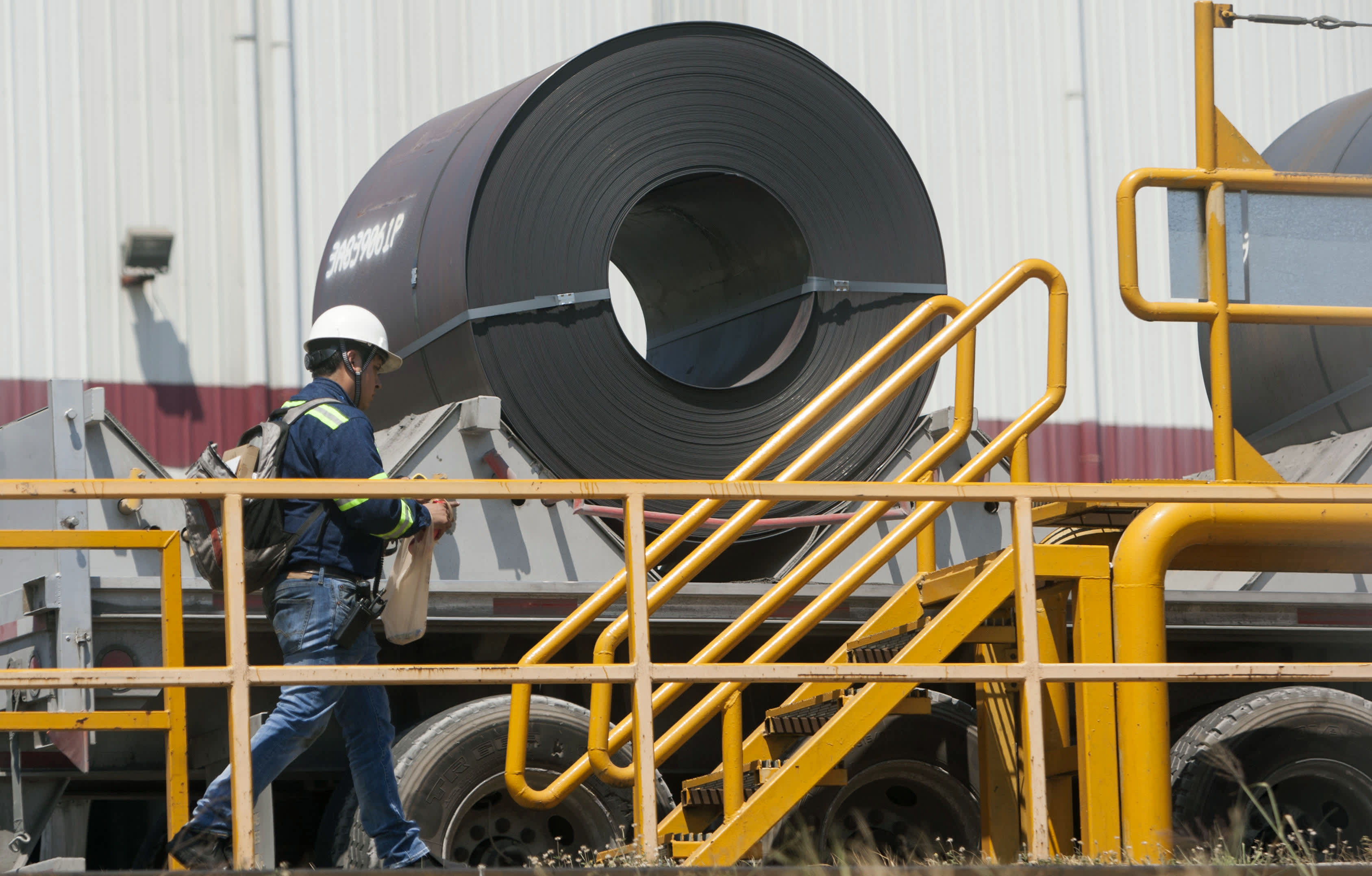 A worker walks past a steel coil loaded on a truck, at a plant in Monterrey, Mexico on August 27, 2018.