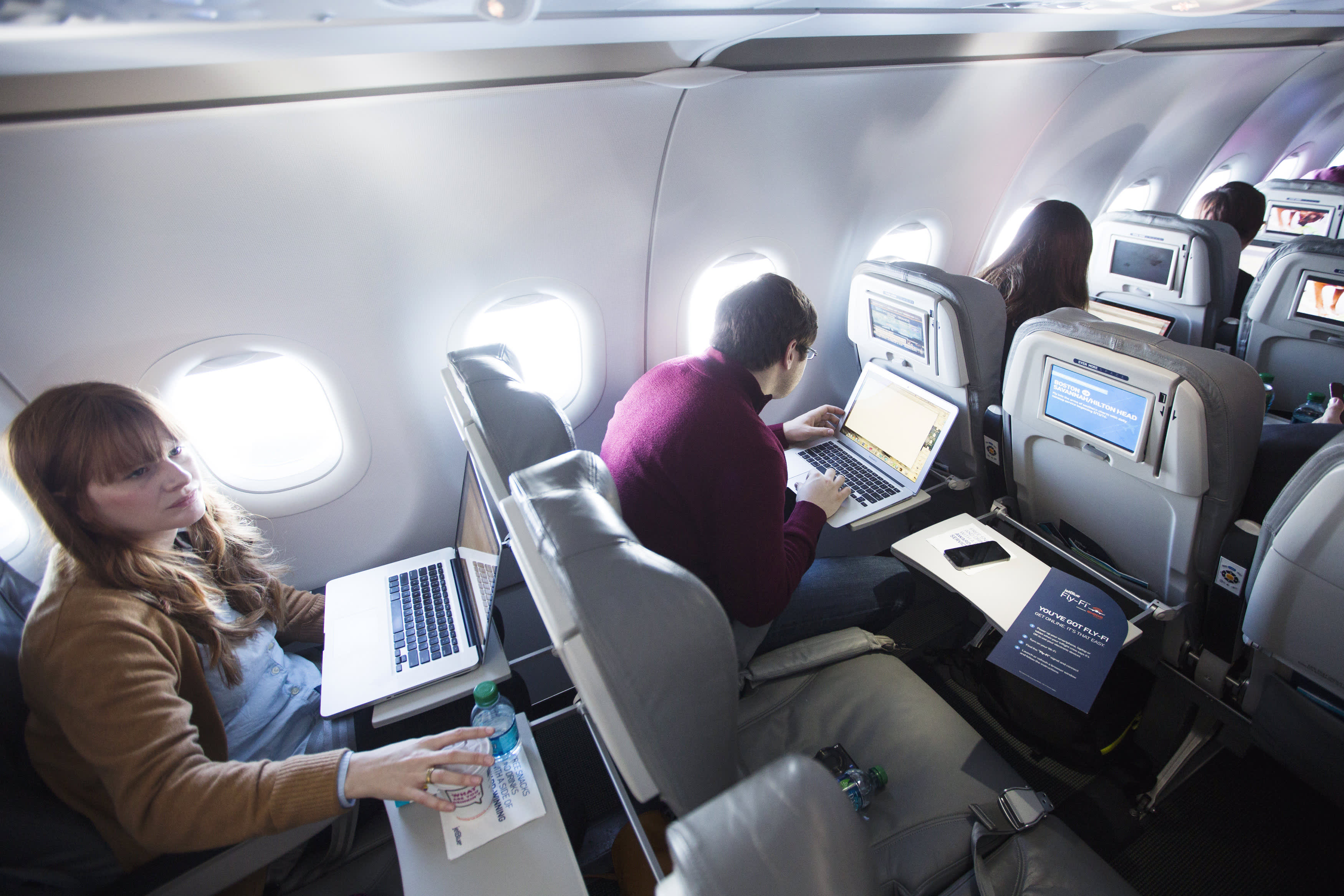 Journalists use their computers to test high speed inflight Internet service on a flight out of John F. Kennedy International Airport in New York.