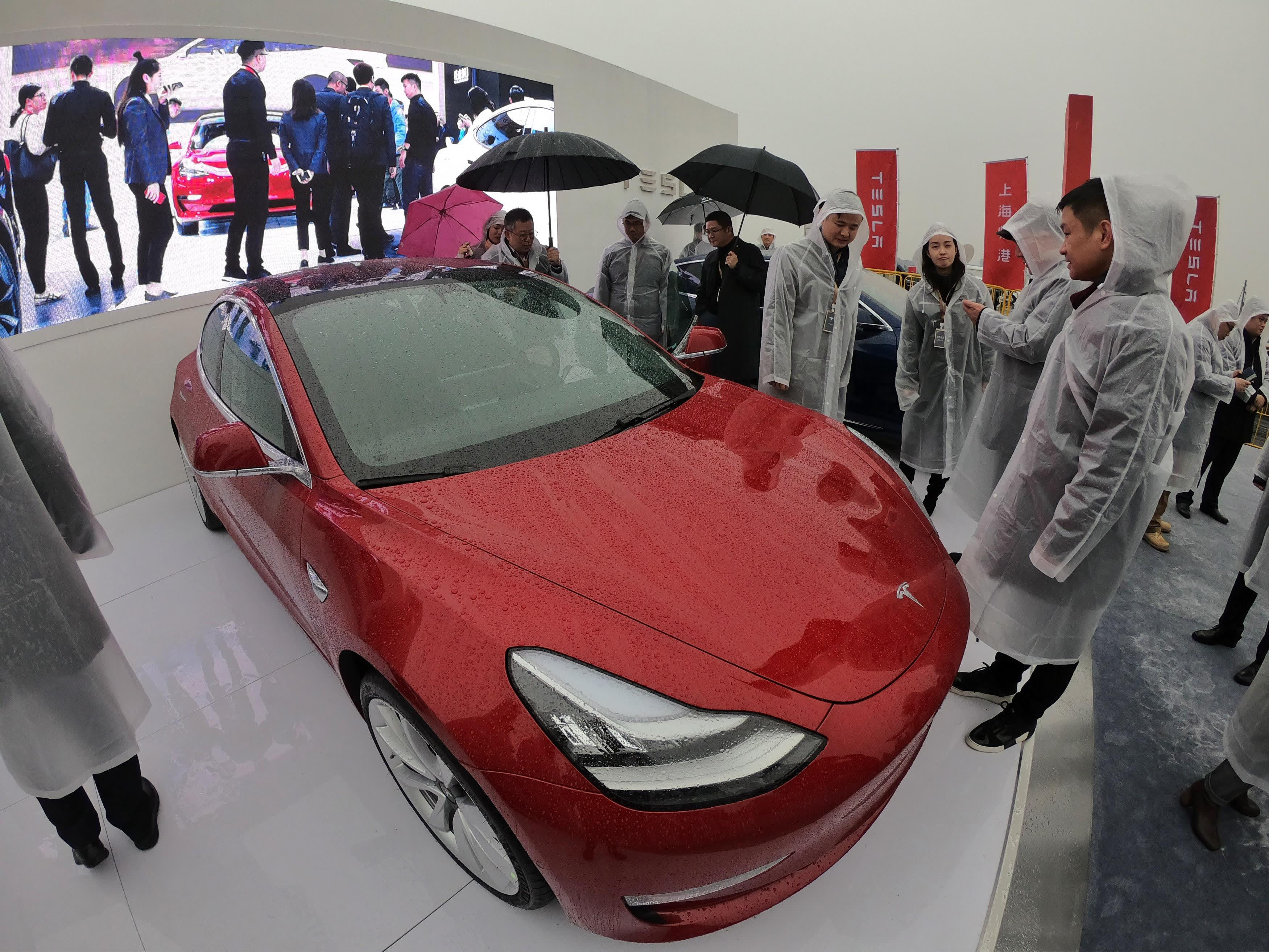 Guests look at a Tesla Model 3 during a ground-breaking ceremony for a Tesla factory in Shanghai on January 7, 2019.