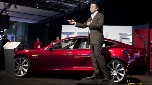 Elon Musk, chairman and chief executive officer of Tesla Motors, speaks in front of a Tesla Model S electric car on day two of the 2010 North American International Auto Show in Detroit, Michigan.