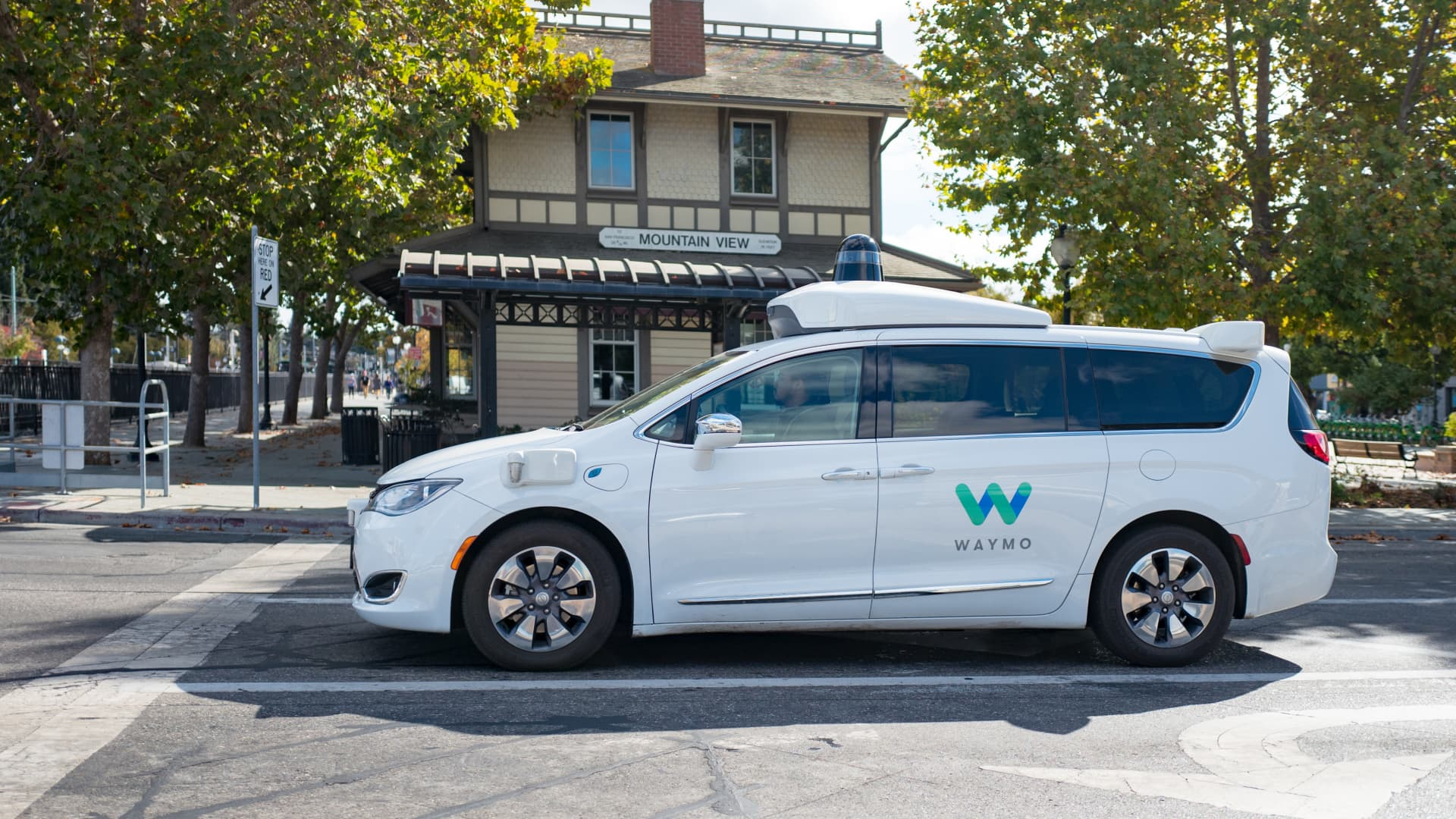 Close-up of self driving minivan, with LIDAR and other sensor units and logo visible, part of Google parent company Alphabet Inc, driving past historic railroad station with sign reading Mountain View, in the Silicon Valley town of Mountain View, California, with safety driver visible, October 28, 2018.