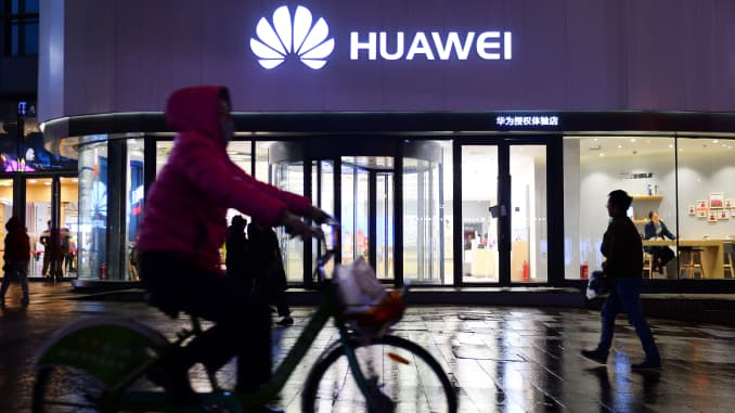 A woman cycles past a Huawei store in Shenyang, China.