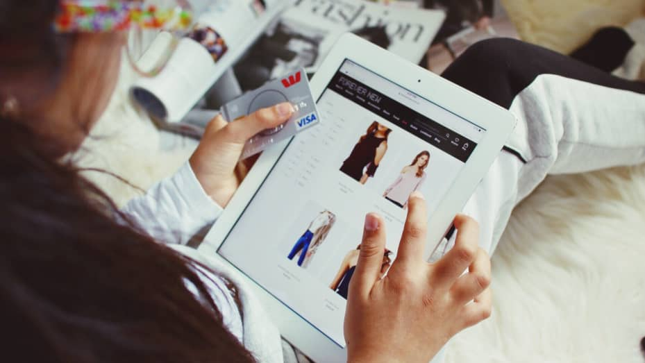 A shopper looks through clothes on her iPad device.