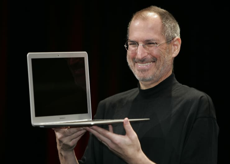 Apple CEO Steve Jobs smiles as he shows the MacBook Air