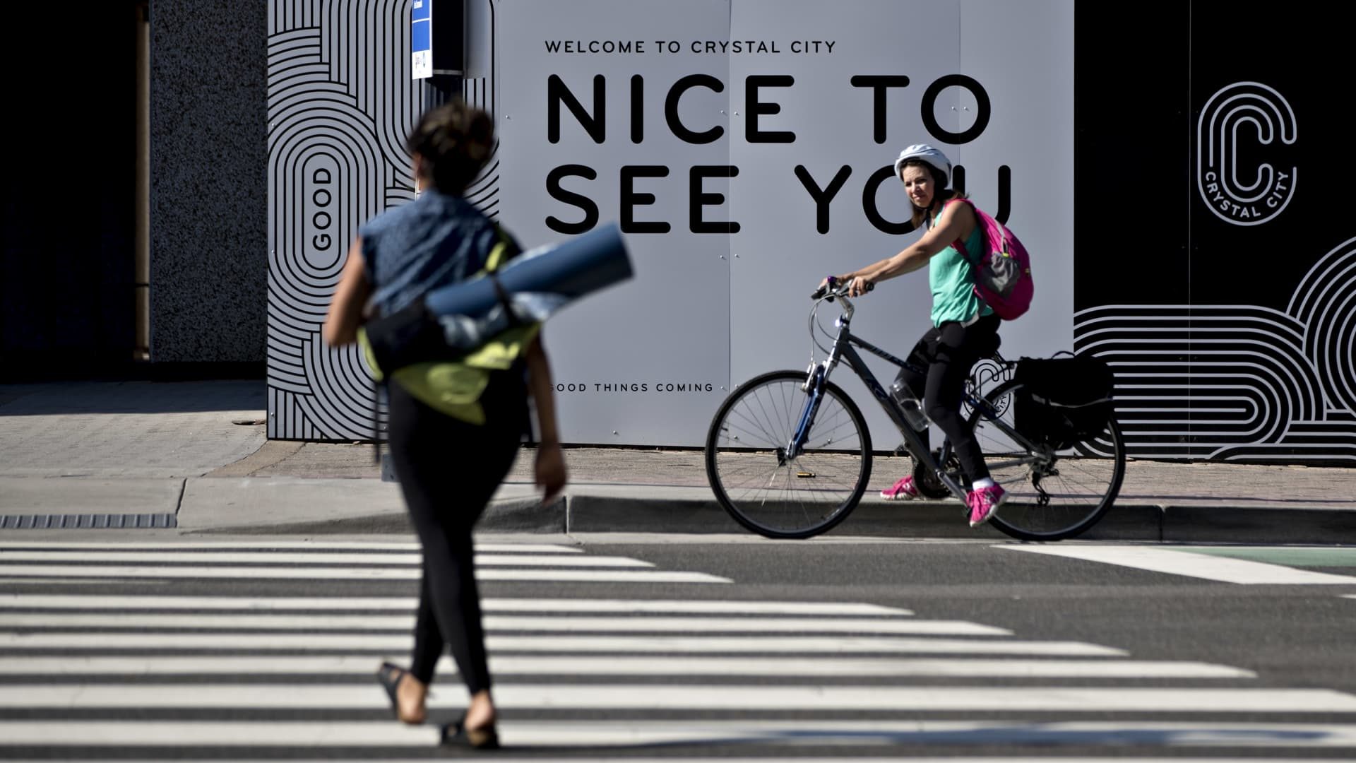A bicyclist stops in front of signage in the Crystal City neighborhood of Arlington, Virginia, on June 28, 2019, the site of Amazon's HQ2.