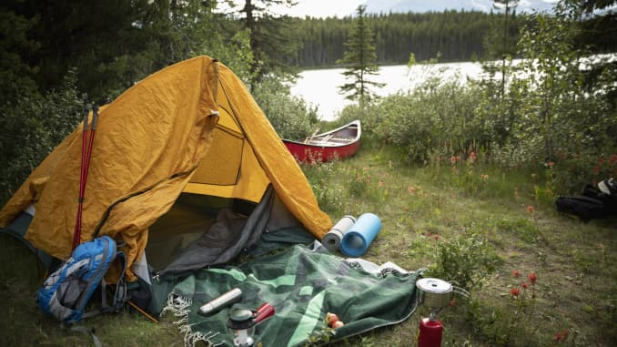 Tent and camping equipment at lakeside forest campsite, Alberta, Canada