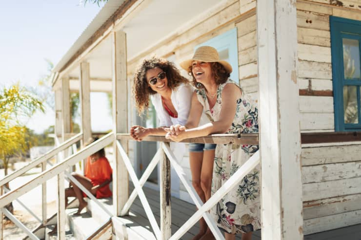GP: Mother and adult daughter relaxing on sunny beach hut patio