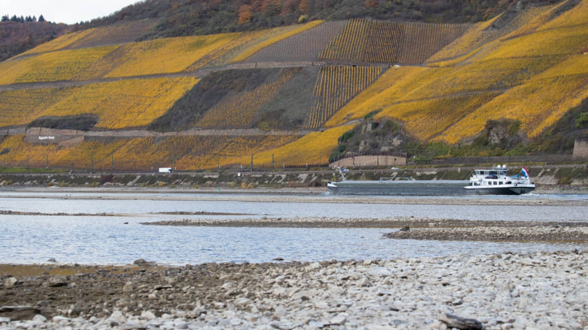 Half loaded cargo ships pass by the low water in the River Rhine along the vineyards on November 13, 2018 in Osterspai near Sankt Goarshausen, Germany. Summer heat wave in Germany as well unfavorable wind conditions, and no rain left the Rhine - which begins in the Swiss Alps, runs through Germany, and empties into the North Sea - at record low water levels.