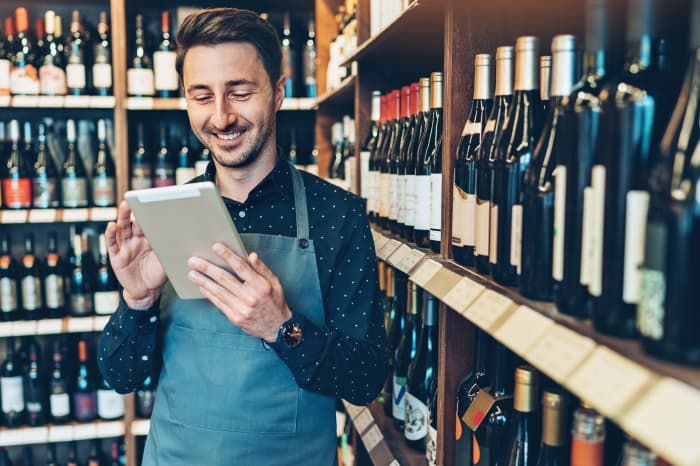 GP: Smiling young man with digital tablet in a wine shop