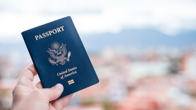 GP: Close-Up Of Hand Holding American Passport Against Townscape