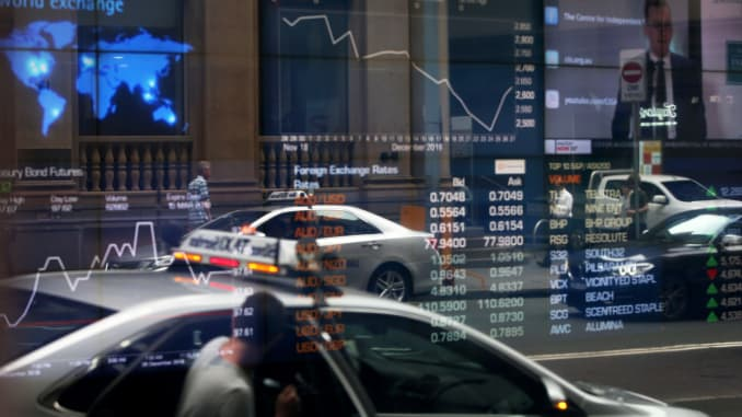 Vehicles are reflected in a window as electronic boards display stock information at the Australian Securities Exchange, operated by ASX.