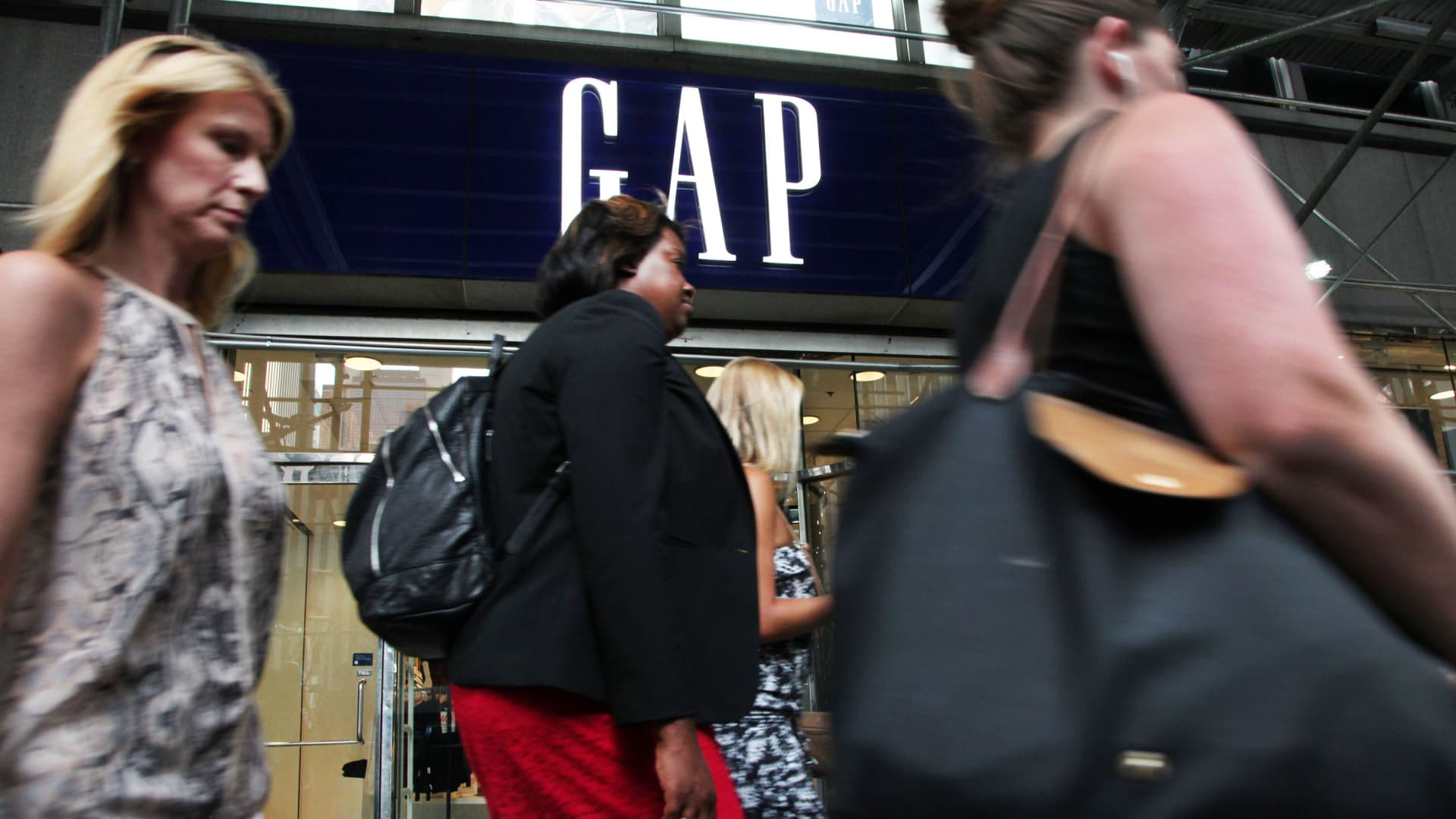 Pedestrians pass in front of a GAP store in New York.