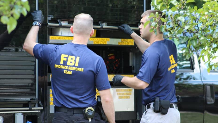 FBI agents finish loading materials into a truck