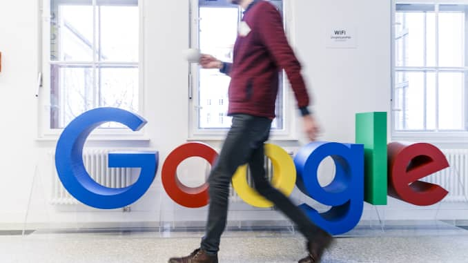 GP: An employee passes the Google logo