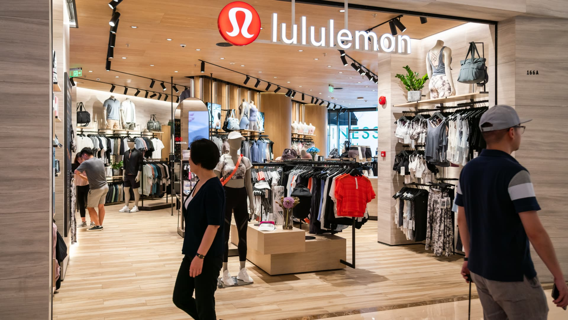 Pedestrians seen walking past Canadian athletic apparel retailer Lululemon in Shanghai.