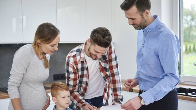 Family with real estate agent signing contract in kitchen of new apartment