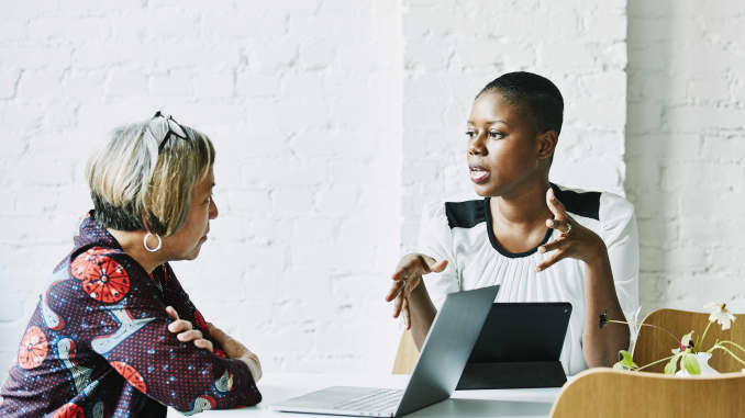 GP: Female financial advisor in discussion with client in office conference room