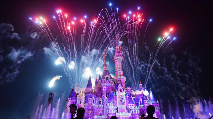 Visitors watch fireworks explode over the Shanghai Disneyland castle at an event to mark the first anniversary of the opening of the park.
