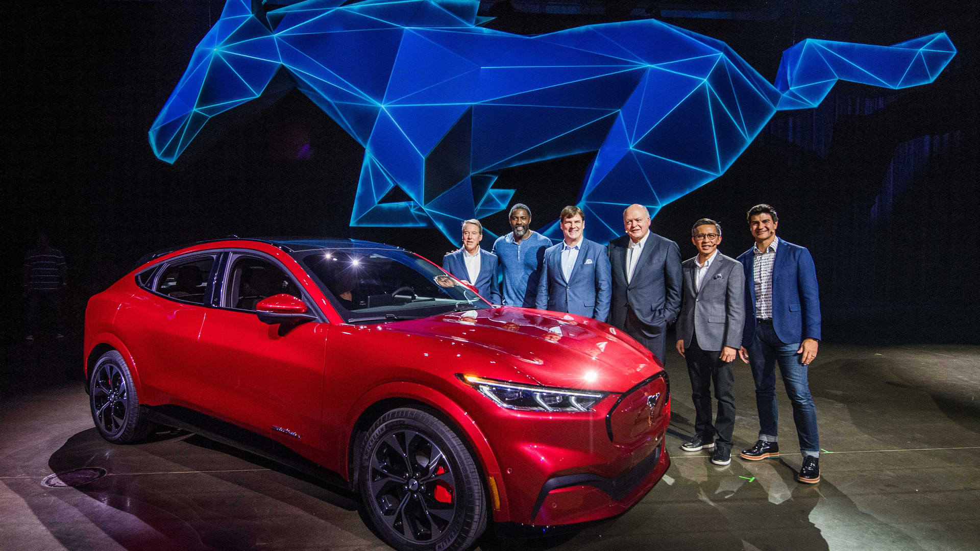 Then-Ford CEO James Hackett (3rd R) and team members, including his successor, Jim Farley (3rd L), reveal the company's first mass-market electric car the Mustang Mach-E, which is an all-electric vehicle that bears the name of the company's iconic muscle car at a ceremony in Hawthorne, California on November 17, 2019.