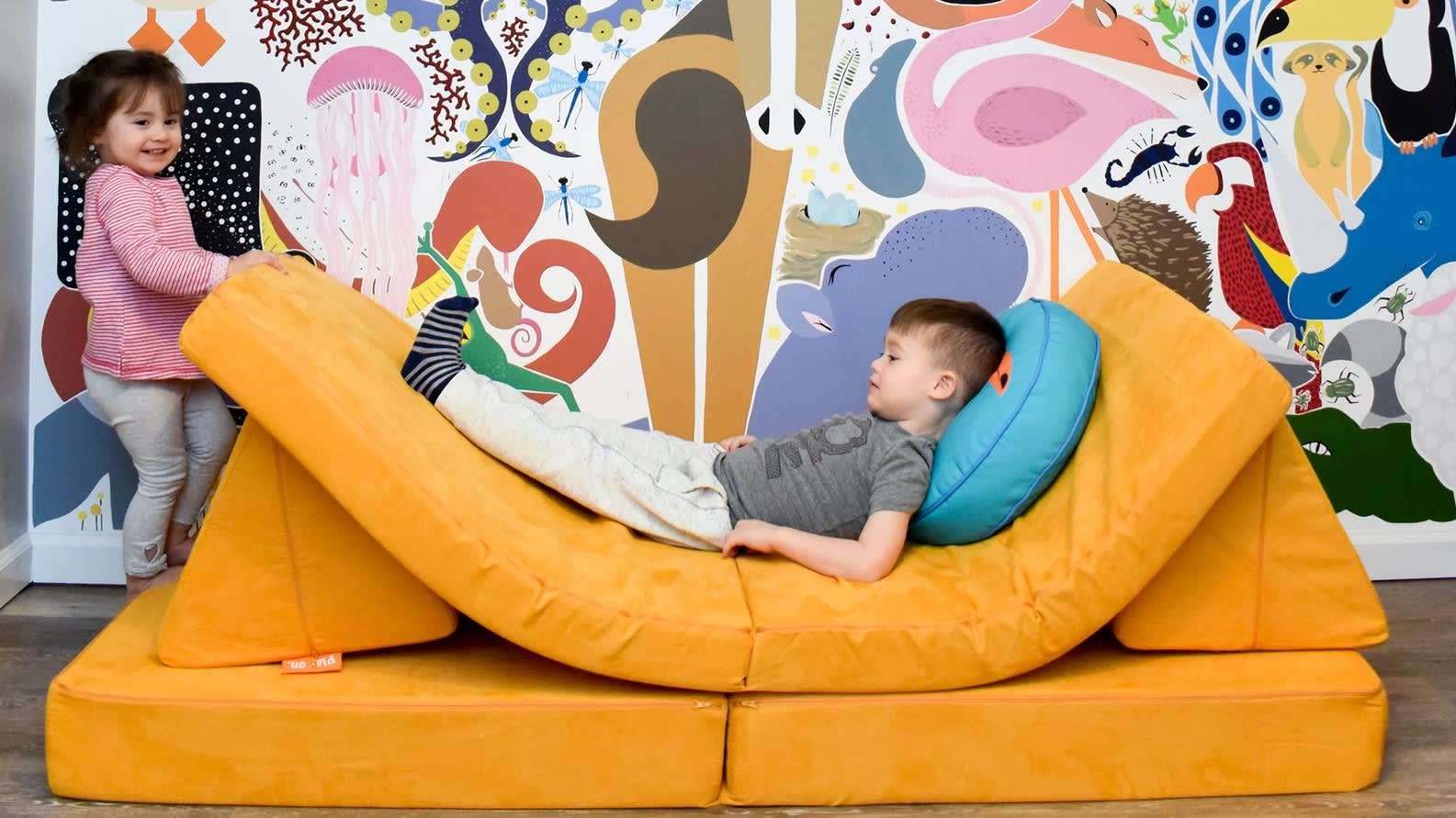 The infinitely configurable play couch made up of four foam pieces: base, cushion, and two triangle pillows.