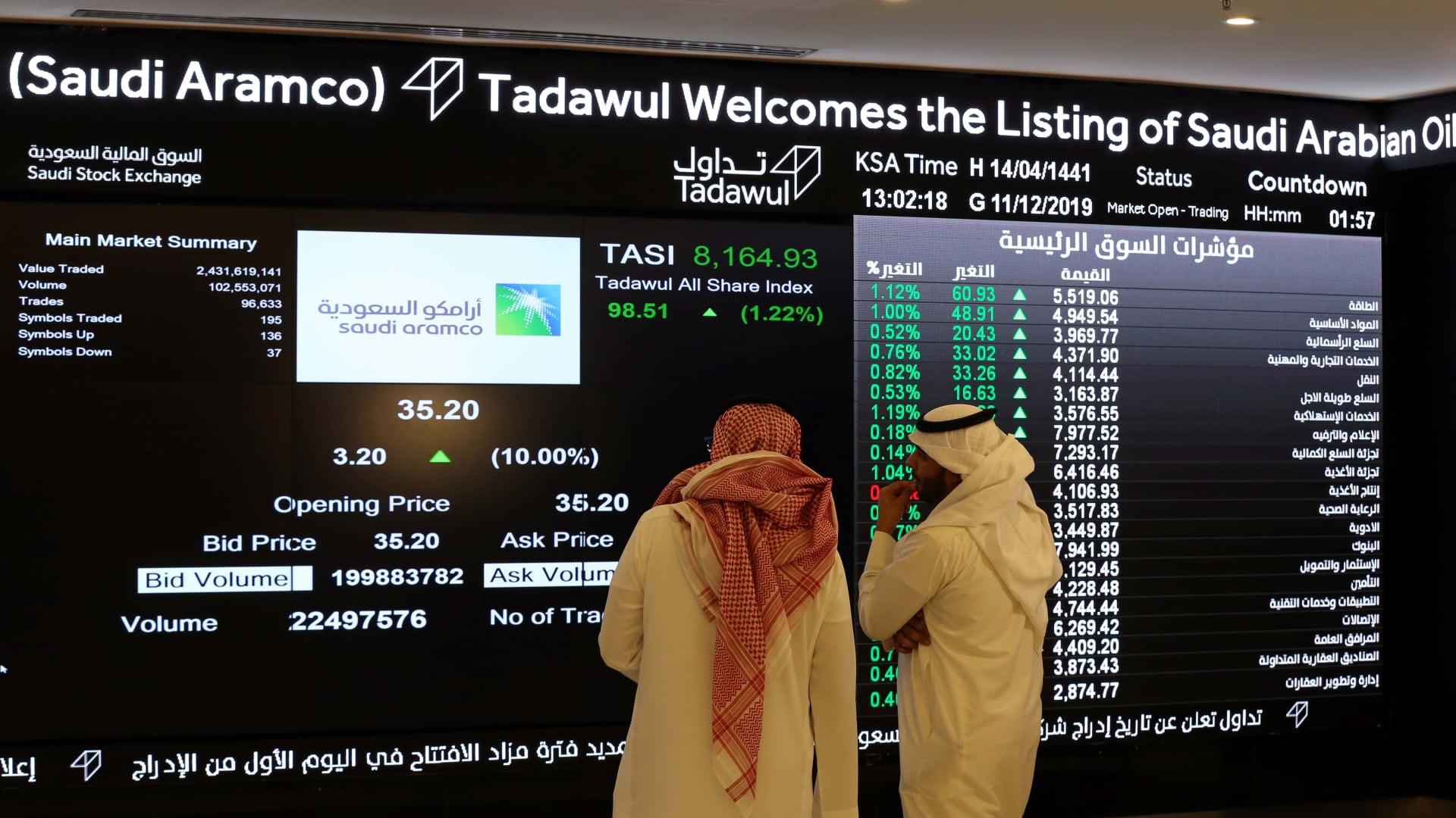 Investors monitor a screen displaying stock information at the Saudi Stock Exchange (Tadawul) following the debut of Saudi Aramco's initial public offering (IPO) on the Riyadh's stock market, in Riyadh, Saudi Arabia, December 11, 2019.