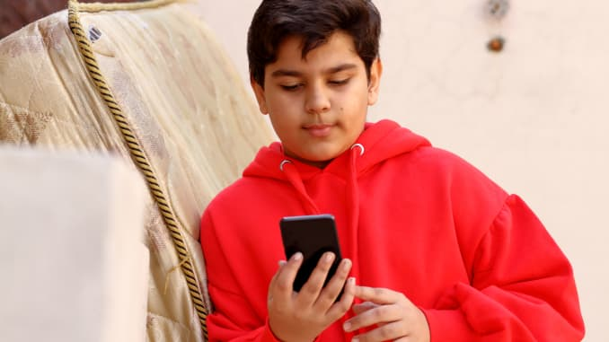 Young boy using mobile phone in winter clothing
