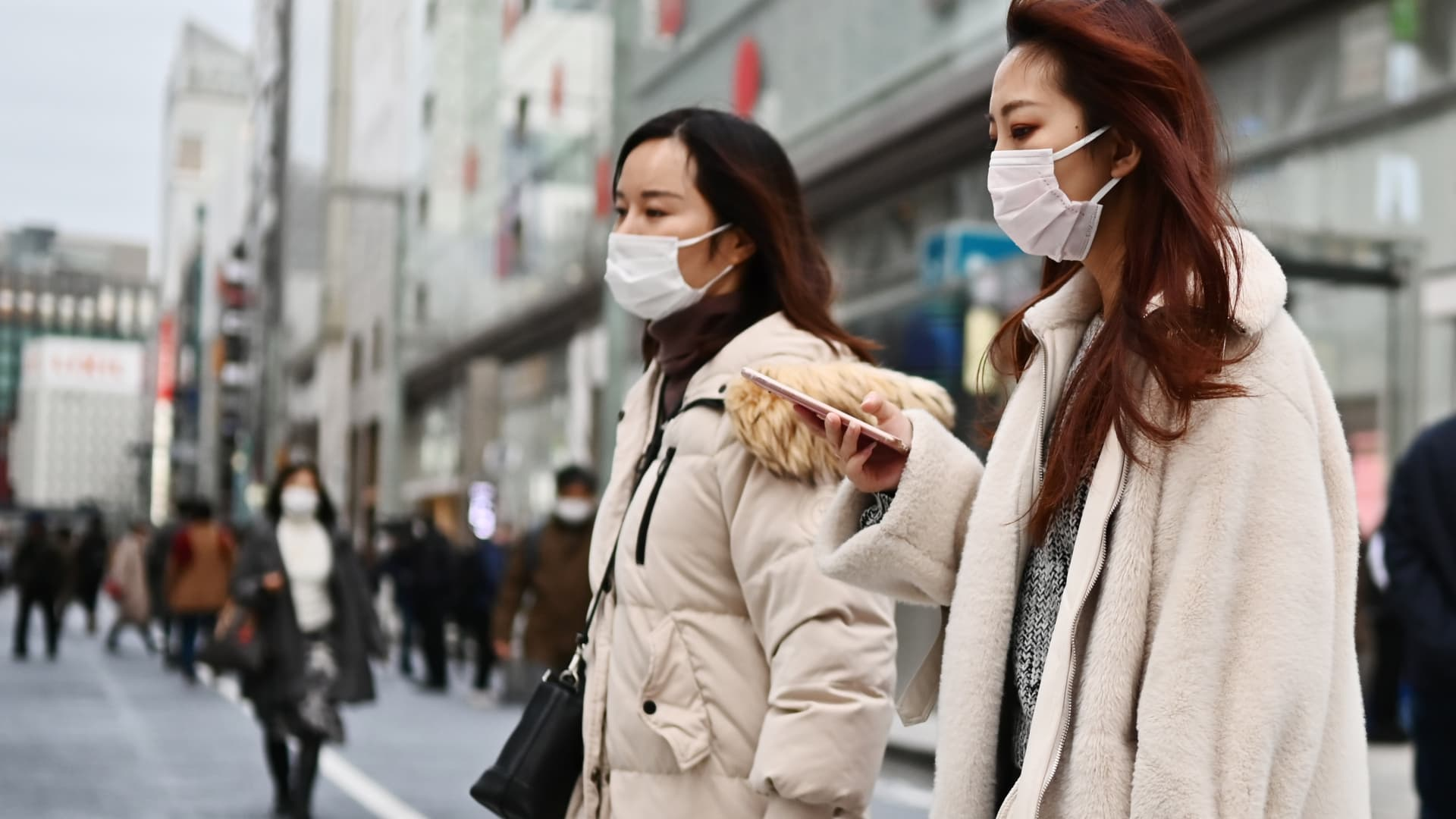 Pedestrians wearing protective masks to help stop the spread of a deadly virus which began in the Chinese city of Wuhan, walk on a street in Tokyo's Ginza area on January 25, 2020.