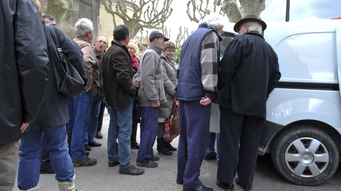 A line forms at an open car trunk at the Richerenches truffle market.