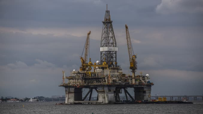 A kayaker passes in front of an offshore oil platform in the Guanabara Bay in Niteroi, Brazil, Saturday, Feb. 1, 2020.
