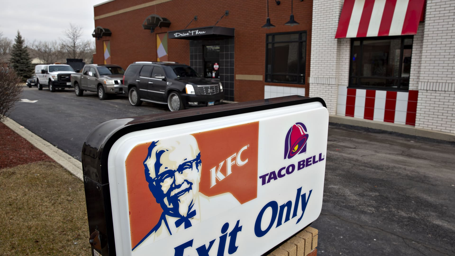 Vehicles wait in line at the drive through lane of a Yum! Brands Inc. Kentucky Fried Chicken (KFC) and Taco Bell restaurant in Lockport, Illinois, U.S.