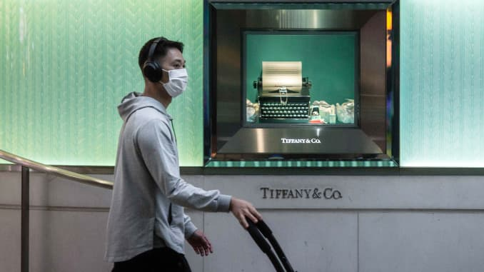 A pedestrian wears a face mask while pushing a stroller past the Tiffany & Co. luxury goods store at Times Square in the Causeway Bay district of Hong Kong, China, on Feb. 6, 2020.