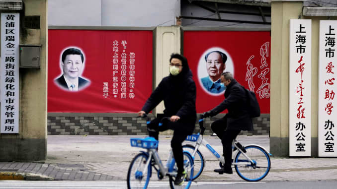 People wearing masks pass by portraits of Chinese President Xi Jinping and late Chinese chairman Mao Zedong as the country is hit by an outbreak of the novel coronavirus, on a street in Shanghai, China February 10, 2020.