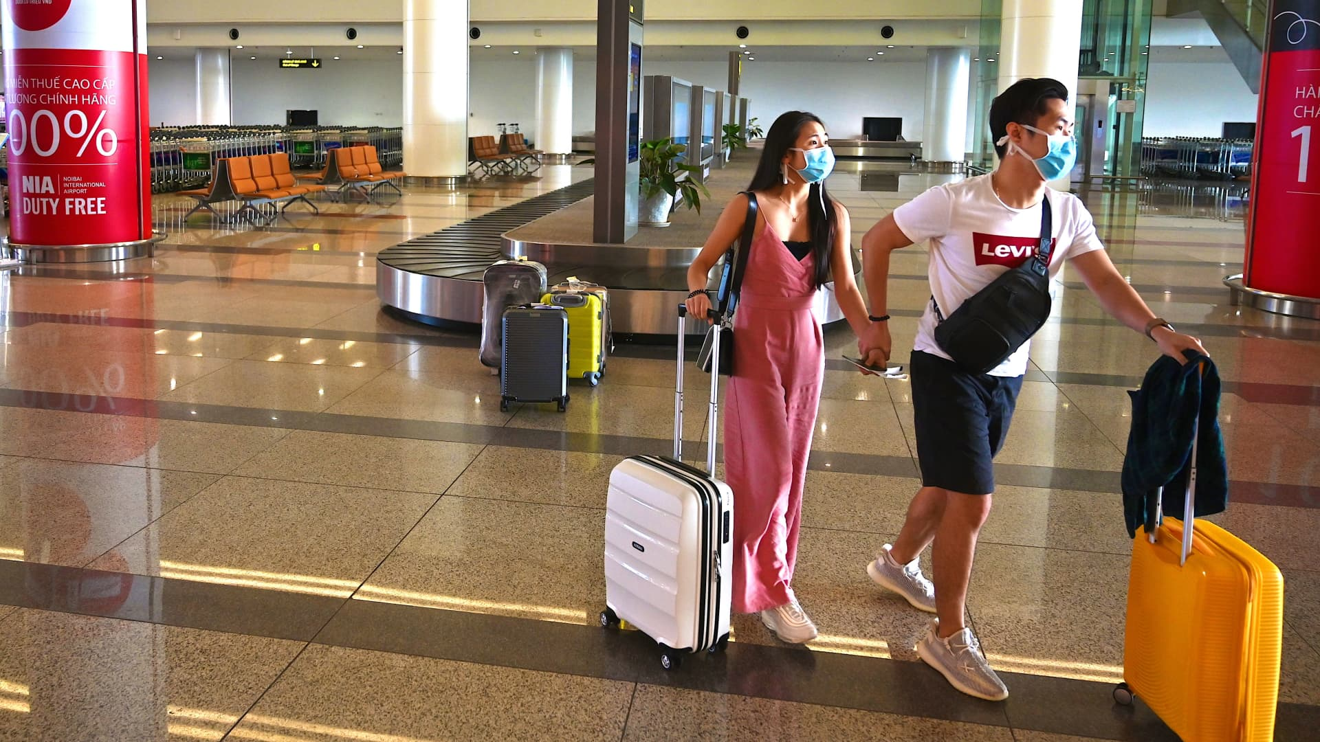 Passengers with protective face masks walk with their luggage in the empty arrival hall of Noi Bai International Airport in Hanoi, Vietnam.
