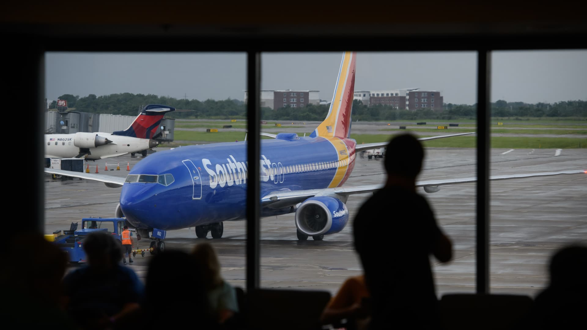 A person watches as a Southwest Airlines Co. plane arrives at a gate at the Pittsburgh International Airport (PIT) in Moon Township, Pennsylvania, U.S., on Tuesday, July 2, 2019.
