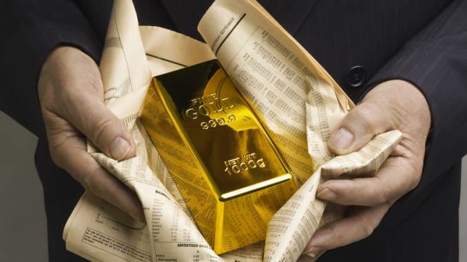 A gold bar is wrapped in a financial newspaper.