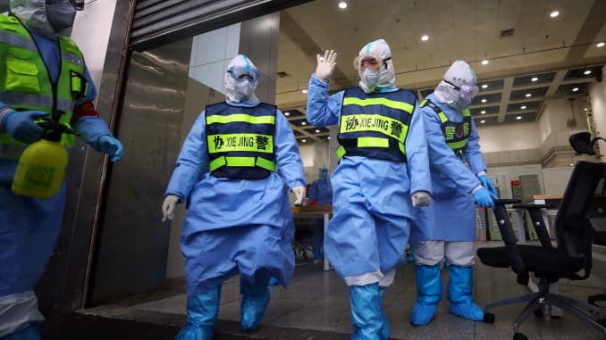 Government workers walk out of Jianghan Fangcang temporary hospital for COVID-19 patients, which is being shut down, in Wuhan in central China's Hubei province Monday, March 09, 2020. As the number of patients drops, the city has begun closing the temporary hospitals built to treat patients with the coronavirus.