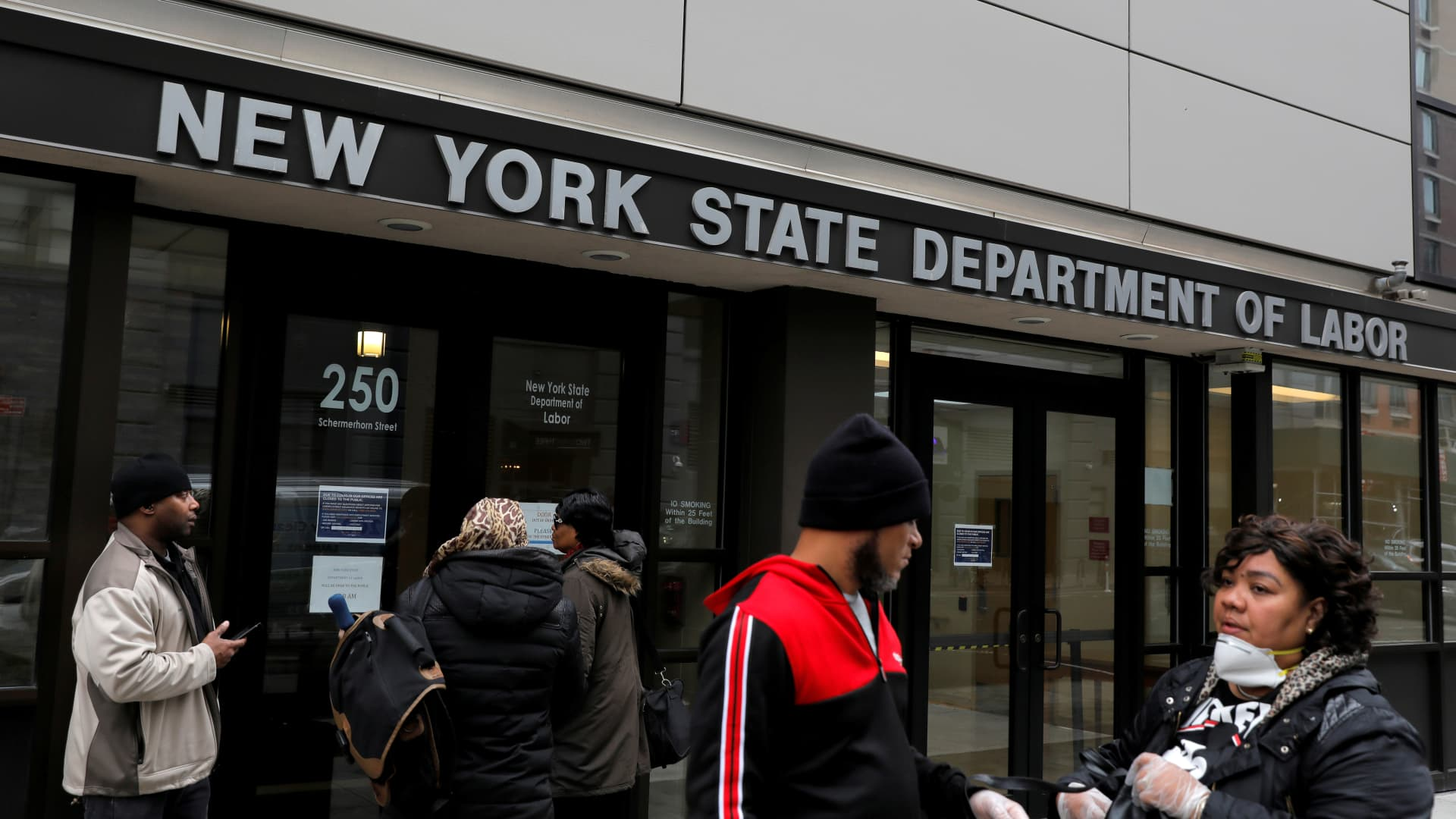 People gather at the entrance for the New York State Department of Labor offices in Brooklyn on March 20, 2020. The Federal Reserve estimates that 47 million people could lose their jobs before the COVID-19 crisis ends.