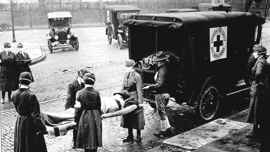 Các thành viên của Red Cross Motor Corps, tất cả đều đeo khẩu trang chống lại sự lây lan thêm của dịch cúm, khiêng một bệnh nhân trên cáng vào xe cứu thương của họ, Saint Louis, Missouri, tháng 10 năm 1918.