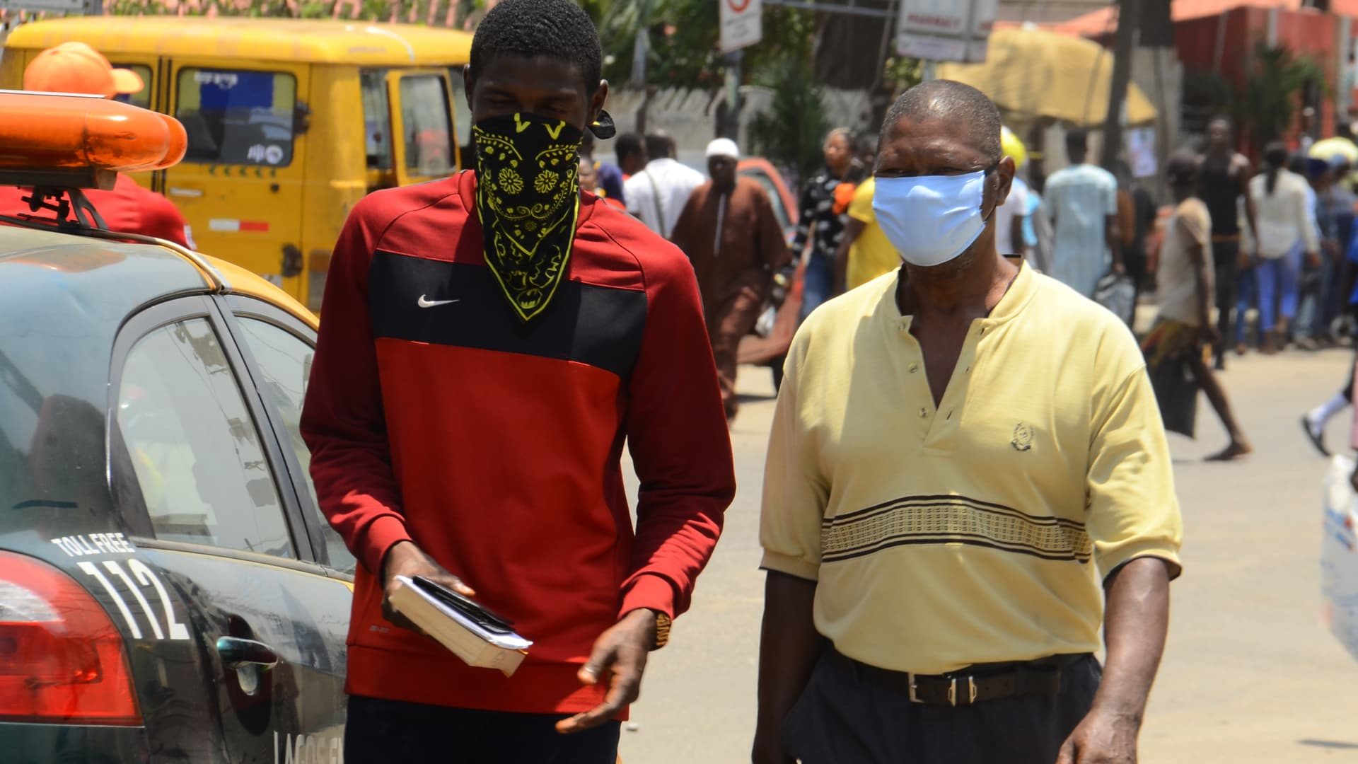 Commuters wearing a protective face masks walk on the street of Lagos, as a preventive measure against the spread of the new corona virus, COVIC-19, in Lagos, on March 26, 2020.