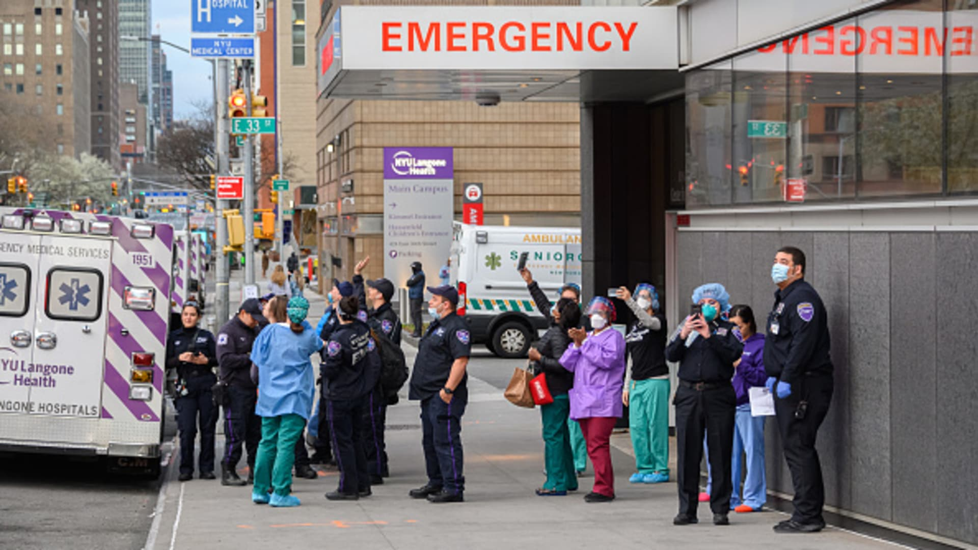 Medical personnel are seen outside NYU Langone Health hospital as people applaud to show their gratitude to medical staff and essential workers working on the front lines of the coronavirus pandemic as the country works to stop the spread of COVID-19 on April 4, 2020 in New York City.