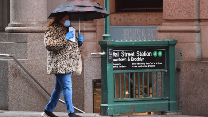 A woman walks by the Wall Street subway station sign on March 23, 2020 in New York City.