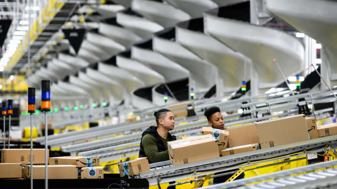 Men work at a distribution station in the 855,000-square-foot Amazon fulfillment center in Staten Island, New York.