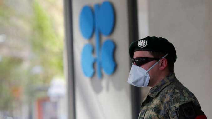 An Austrian army member stands next to the logo of the Organization of the Petroleoum Exporting Countries (OPEC) in front of OPEC's headquarters in Vienna, Austria April 9, 2020.
