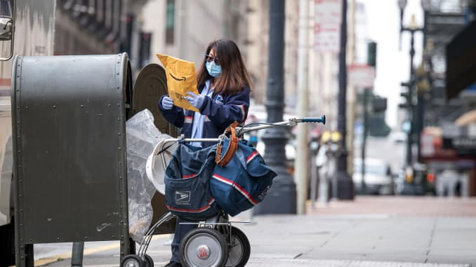 A United States Postal Service (USPS) employee wearing a protective mask loads an Amazon.com Inc. package into a mail cart in San Francisco, California, U.S., on Monday, April 6, 2020.