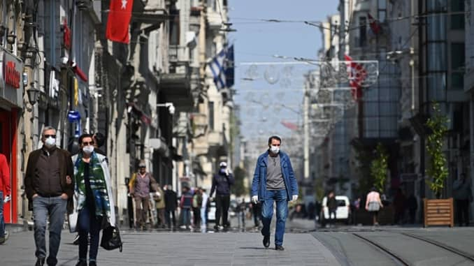 People wear face masks as they walk down the Istiklal avenue on April 14, 2020 in Istanbul a day after Turkish President ordered a fresh lockdown next weekend, warning the move would be imposed as long as necessary to stop the spread of the COVID-19 disease caused by the novel coronavirus.