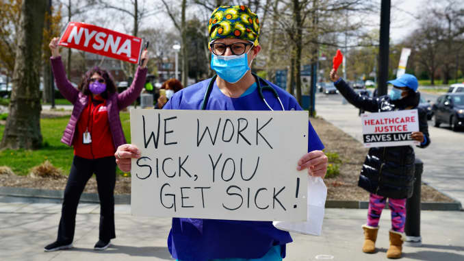 Public health workers, doctors and nurses protest over lack of sick pay and personal protective equipment (PPE) outside a hospital in the borough of the Bronx on April 17, 2020 in New York, NY.
